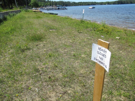 The Beach At Sherman Park, Recently Placed Sign Stapled To A Pole, And An Official Metal No Swimming Sign By The Water